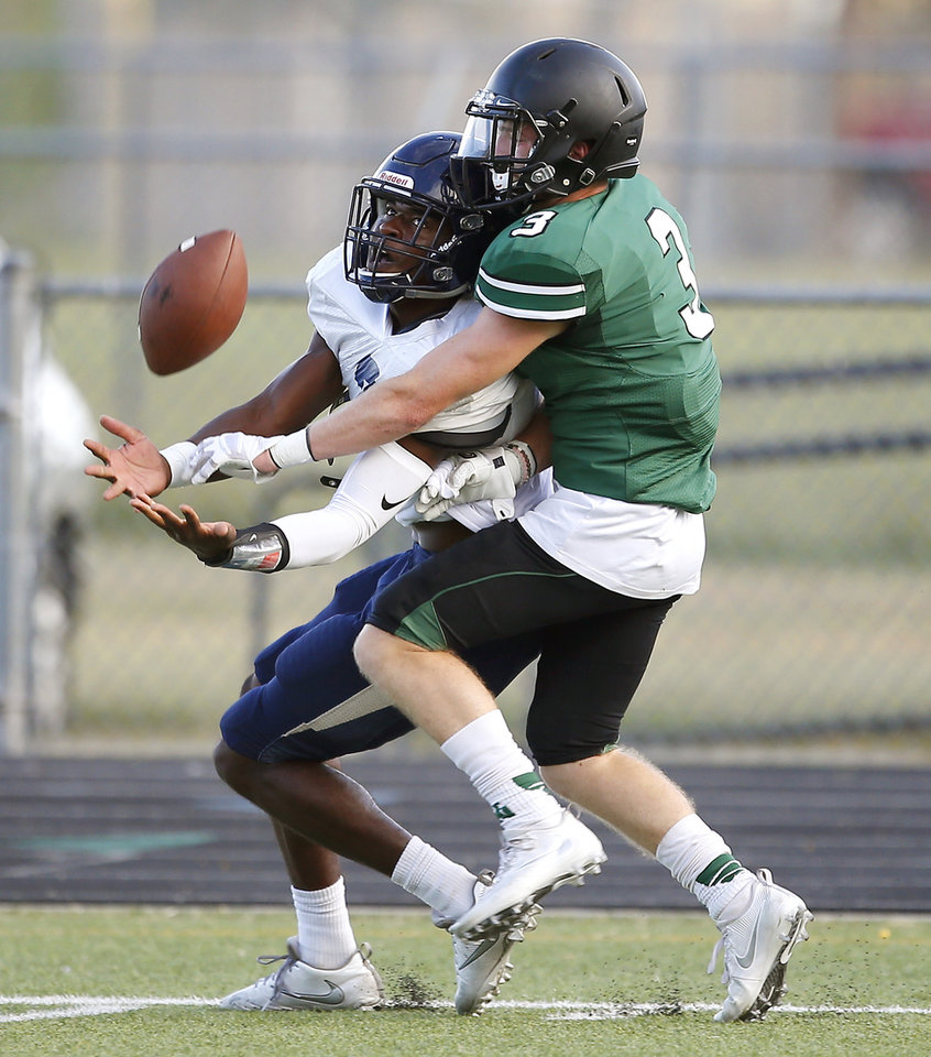 Photo - Southmoore's Gervarrius Owens catches apsss in front of Norman North's Isaac Stoops  during a scrimmage at Midwest City High School on Friday, August 19, 2016. Photo by Bryan Terry, The Oklahoman