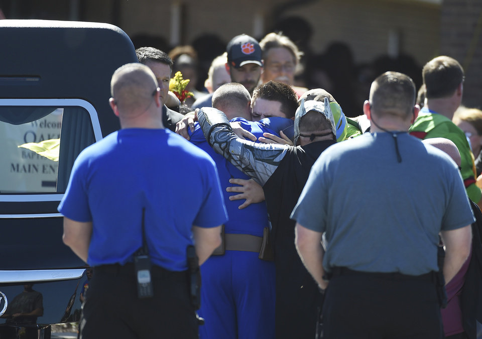 Photo - Pallbearers hug each other after placing the body of Jacob Hall into a hearse during a superhero-themed funeral service for him at Oakdale Baptist Church on Wednesday, Oct. 5, 2016, in Townville, S.C.   A 14-year-old boy killed his own father, then drove to Townville Elementary and fired on two children and a teacher as recess began.  Jacob died Saturday.  (AP Photo/Rainier Ehrhardt)