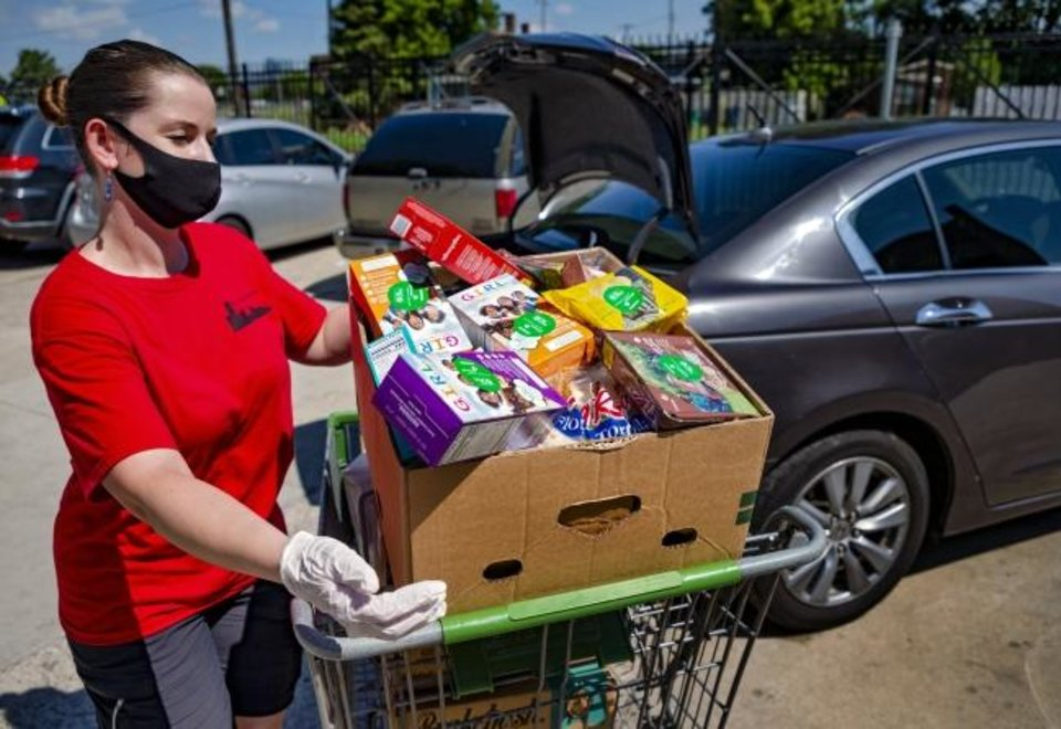Photo -  Skyline Urban Ministry's Laura Sikes loads a cart of food in a car with cookies donated by Girl Scouts of Western Oklahoma and the United Way on Wednesday. [Chris Landsberger/The Oklahoman]