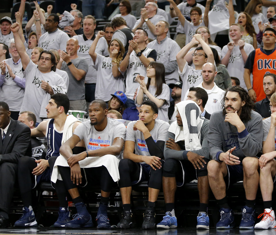Photo - From left, Oklahoma City's Enes Kanter, Kevin Durant, Andre Roberson, Dion Waiters and Steven Adams (12) sit on the bench as San Antonio fans cheer during Game 1 of the second-round series between the Oklahoma City Thunder and the San Antonio Spurs in the NBA playoffs at the AT&T Center in San Antonio, Saturday, April 30, 2016. San Antonio won 124-92. Photo by Bryan Terry, The Oklahoman