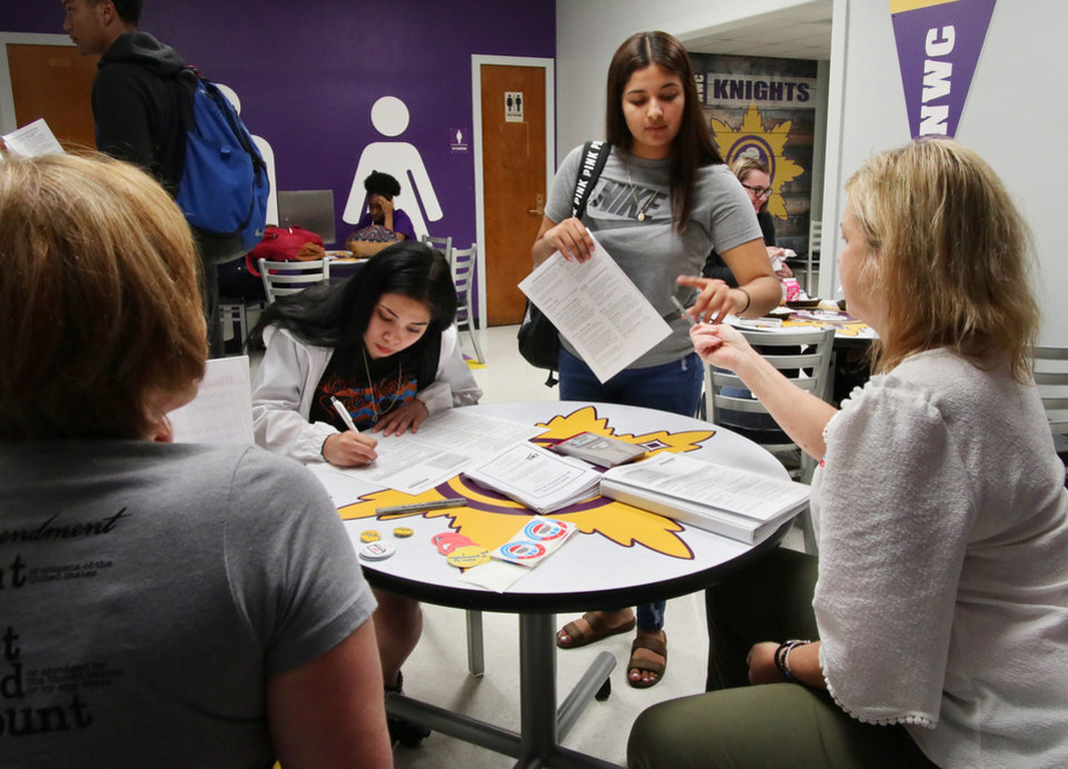 Photo - April Mays, left, and Marti Troy help Magaly Ramirez, 17, standing, and Diamond Alvarez, 18, register to vote.Generation Citizen set up at Northwest Classen High School during lunch to register students age 17 and older to vote, Wednesday, September 25, 2019. [Doug Hoke/The Oklahoman]
