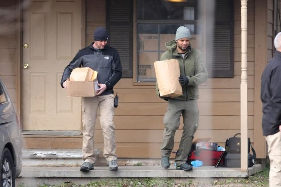 Photo -  Investigators remove items from the scene of a suspected mass homicide where at least 5 children were slain Tuesday, Feb. 2, 2021 in Muskogee, Okla. [Photo by Mike Simons, Tulsa World]