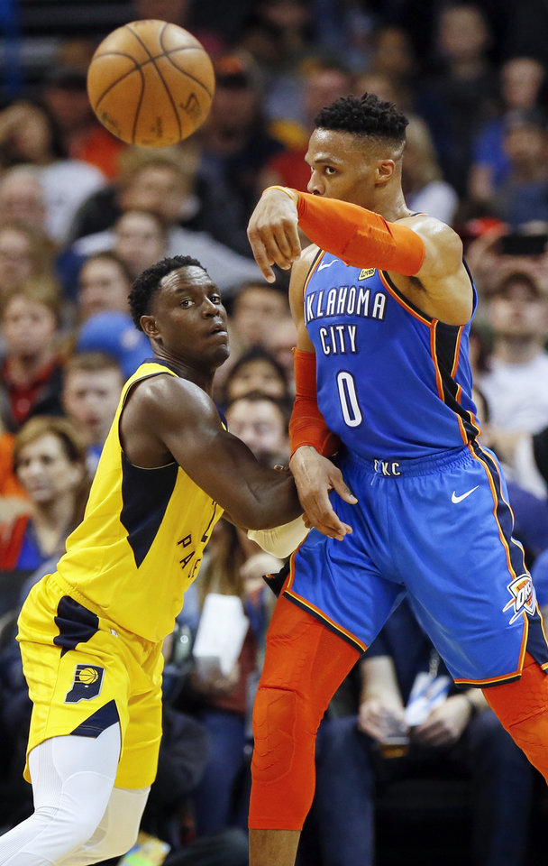 Photo - Oklahoma City's Russell Westbrook (0) passes away from Indiana's Darren Collison (2) during an NBA basketball game between the Indiana Pacers and the Oklahoma City Thunder at Chesapeake Energy Arena in Oklahoma City, Wednesday, March 27, 2019. Oklahoma City won 107-99. Photo by Nate Billings, The Oklahoman