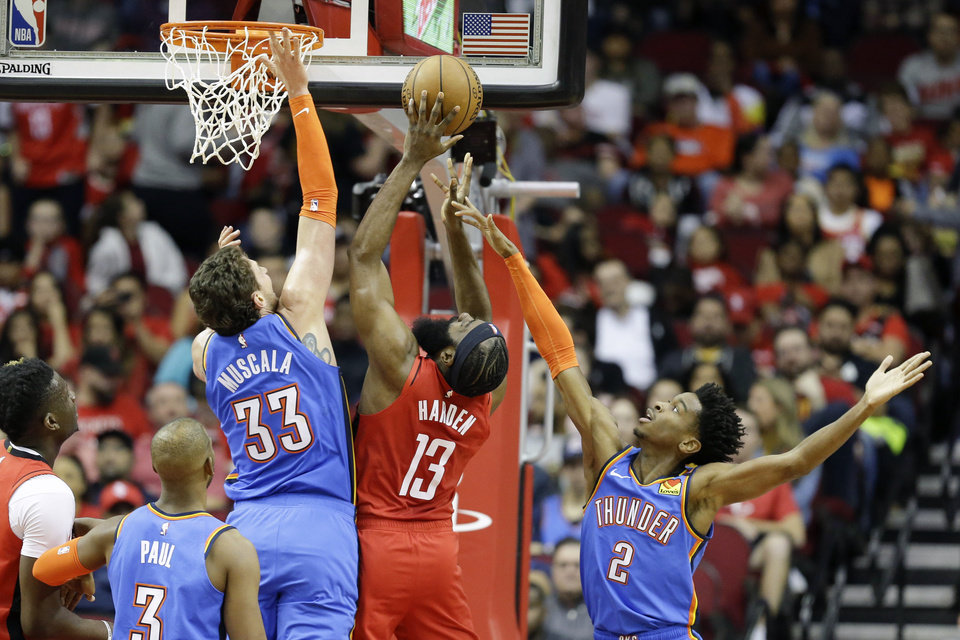 Photo - Houston Rockets guard James Harden (13) shoots as Oklahoma City Thunder forward Mike Muscala (33) and guard Shai Gilgeous-Alexander (2) defend during the first half of an NBA basketball game, Monday, Jan. 20, 2020, in Houston. (AP Photo/Eric Christian Smith)