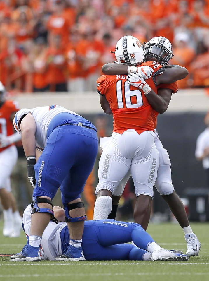 Photo - Oklahoma State's Devin Harper (16) and Calvin Bundage (1) celebrate a quarterback sack next to Boise State's Brett Rypien (4) and John Molchon (77) during a college football game between the Oklahoma State Cowboys (OSU) and the Boise State Broncos at Boone Pickens Stadium in Stillwater, Okla., Saturday, Sept. 15, 2018. OSU won 44-21. Photo by Sarah Phipps, The Oklahoman