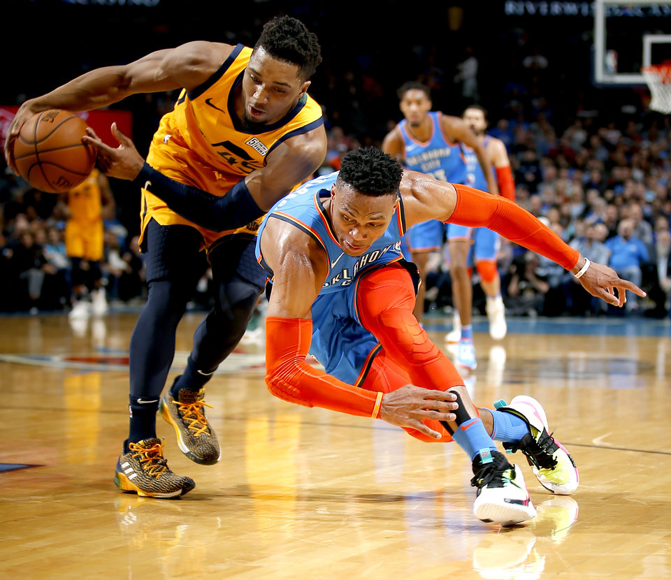 Photo - Oklahoma City's Russell Westbrook (0) and Utah's Donovan Mitchell (45) fight for a loose ball during the NBA game between the Oklahoma City Thunder and the Utah Jazz at the Chesapeake Energy Arena, Friday, Feb. 22, 2019. Photo by Sarah Phipps, The Oklahoman