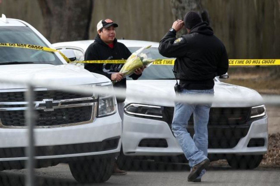 Photo -  A man gives flowers for a memorial to an investigator at the scene of a suspected mass homicide where at least 5 children were slain Tuesday, Feb. 2, 2021 in Muskogee, Okla. [Photo by Mike Simons, Tulsa World]