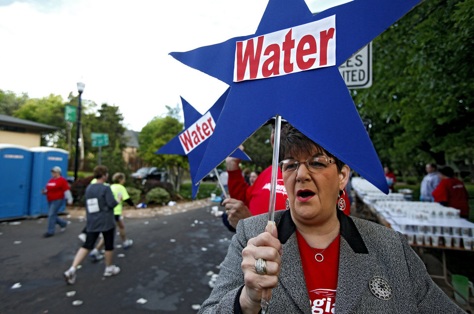 Photo - Supporter Brenda Roberts cheers on runners as she holds up a water sign at a water stop during the tenth anniversary of the 2010 Oklahoma City Memorial Marathon on Sunday, April 25, 2010, in Oklahoma City, Okla.   Photo by Chris Landsberger, The Oklahoman  ORG XMIT: KOD