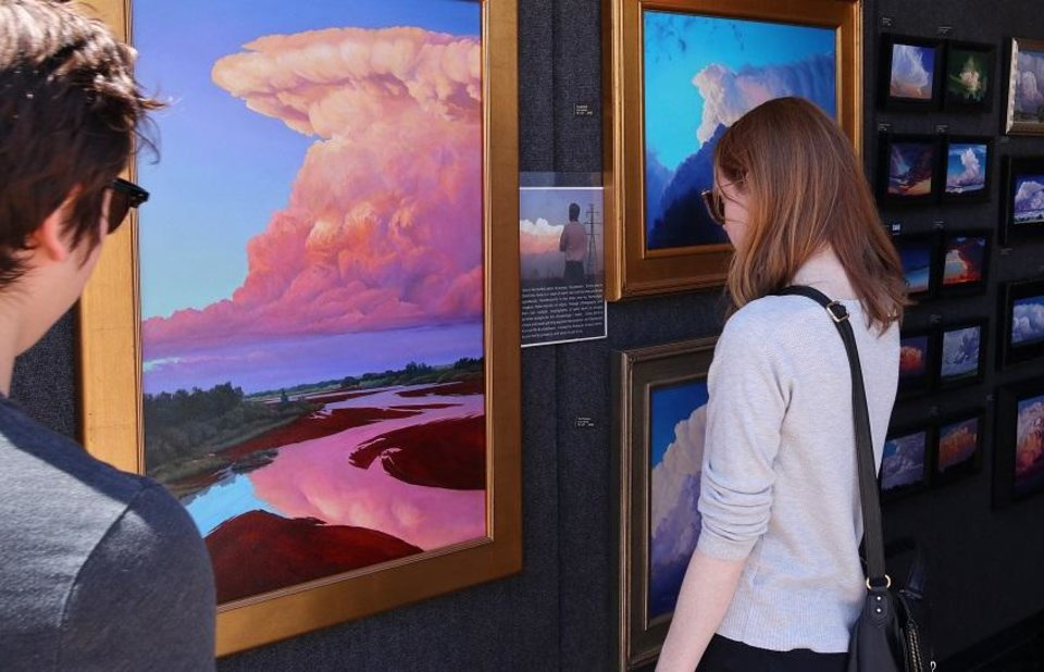 Photo - A couple looks over the paintings of David Holland at the 2018 Festival of the Arts in Bicentennial Park in downtown Oklahoma City, Saturday, April 28, 2018. [Photo by Doug Hoke/The Oklahoman Archives]