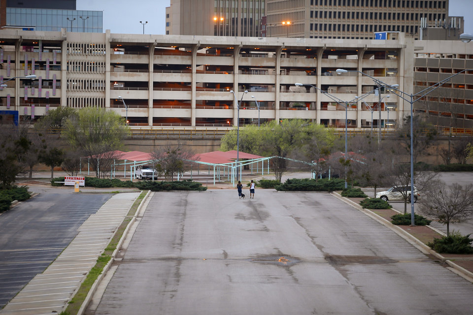 Photo - Two people walk across an empty Bricktown parking lot in Oklahoma City, Friday, March 27, 2020. [Bryan Terry/The Oklahoman]