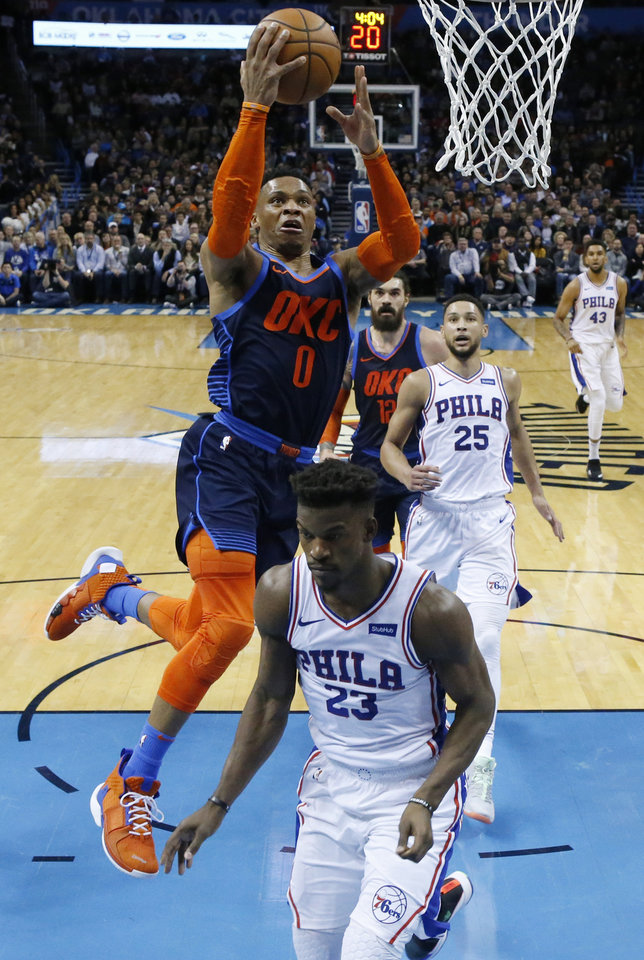 Photo - Oklahoma City Thunder guard Russell Westbrook (0) goes up for a shot between Philadelphia 76ers guards Jimmy Butler (23) and Ben Simmons (25) during the first half of an NBA basketball game Thursday, Feb. 28, 2019, in Oklahoma City. (AP Photo/Sue Ogrocki)