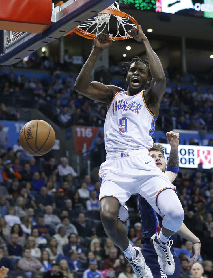 Photo - Oklahoma City Thunder forward Jerami Grant (9) dunks in front of Dallas Mavericks forward Luka Doncic, right, in the second half of an NBA basketball game in Oklahoma City, Monday, Dec. 31, 2018. (AP Photo/Sue Ogrocki)