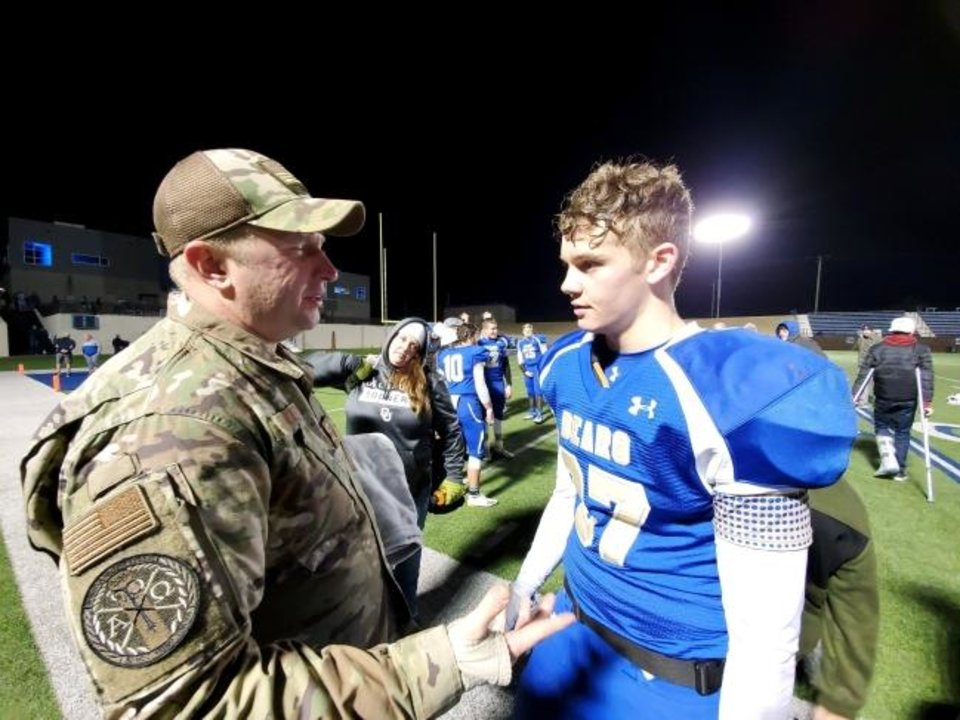 Photo -  Noble's Seth Wall talks with his dad, Doug, after a surprise ceremony Friday night announcing Doug's return from deployment. [PHOTO PROVIDED]