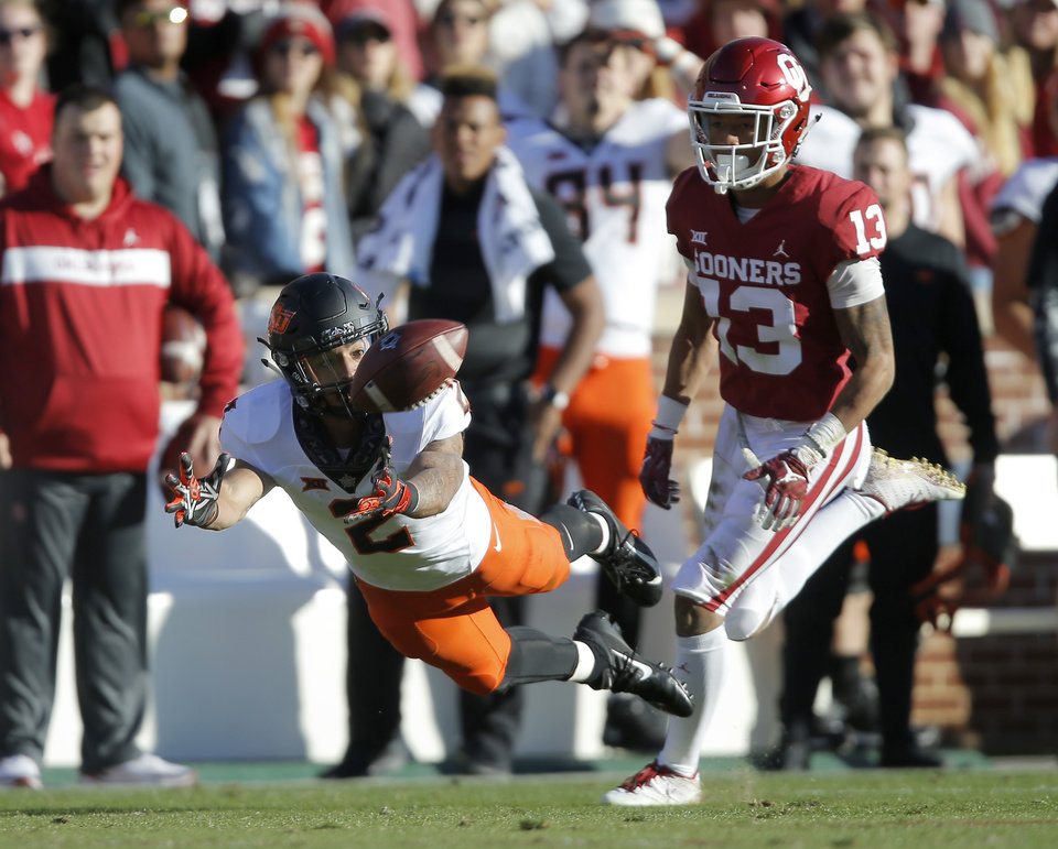 Photo - Oklahoma State's Tylan Wallace (2) misses the ball in front of Oklahoma's Tre Norwood (13) during a Bedlam college football game between the University of Oklahoma Sooners (OU) and the Oklahoma State University Cowboys (OSU) at Gaylord Family-Oklahoma Memorial Stadium in Norman, Okla., Nov. 10, 2018.  Photo by Bryan Terry, The Oklahoman