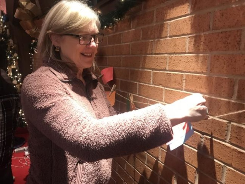 Photo -  Julie Williams, a member of Crown Heights United Methodist Church, hangs a prayer card along the wall during the