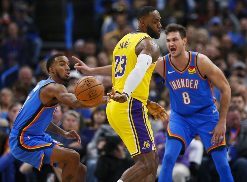 Photo - Los Angeles' LeBron James (23) passes the ball behind his back away from Oklahoma City's Danilo Gallinari (8), right, and Terrance Ferguson (23) in the second quarter during an NBA basketball game between the Oklahoma City Thunder and the Los Angeles Lakers at Chesapeake Energy Arena in Oklahoma City, Friday, Nov. 22, 2019. [Nate Billings/The Oklahoman]