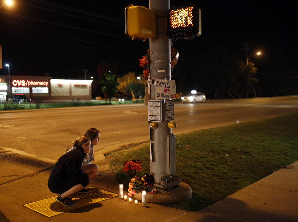 Photo - Oklahoma State students Kelly Cooke, right, and Rebecca Buchanan read messages on a signs at a memorial at Main and Hall of Fame where earlier a car crashed into spectators during the Oklahoma State University homecoming parade killing 4 people and injured several in Stillwater, Okla., Saturday, Oct. 24, 2015. Photo by Sarah Phipps, The Oklahoman