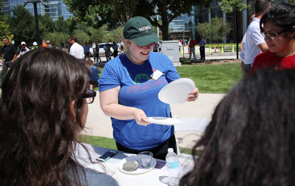 Photo - Myriad Garden staffer Megan Brown demonstrates how to use a pinhole to view the eclipse during the great American solar eclipse party on the Great Lawn of the Myriad Botanical Gardens Monday, August 21, 2017. Photo by Doug Hoke, The Oklahoman