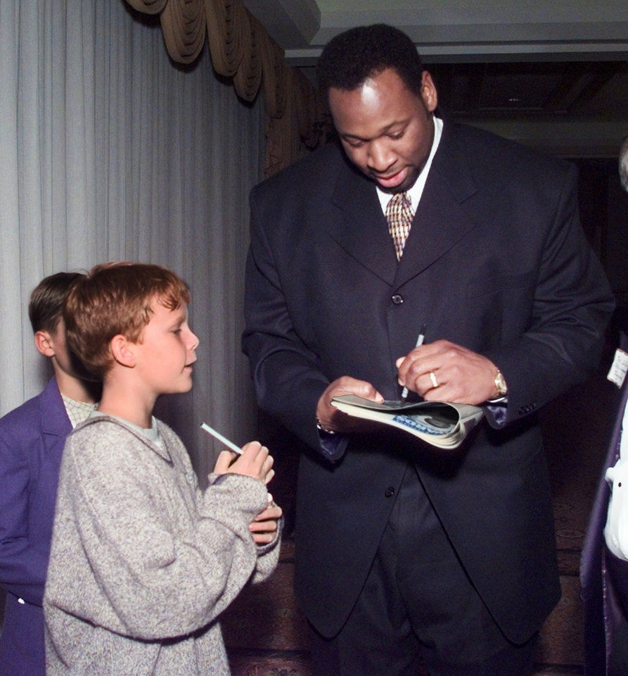Photo - Wayman Tisdale signs an autograph for Jeb Raulston of Oklahoma City before the March of Dimes Sports Headliner Banquet.