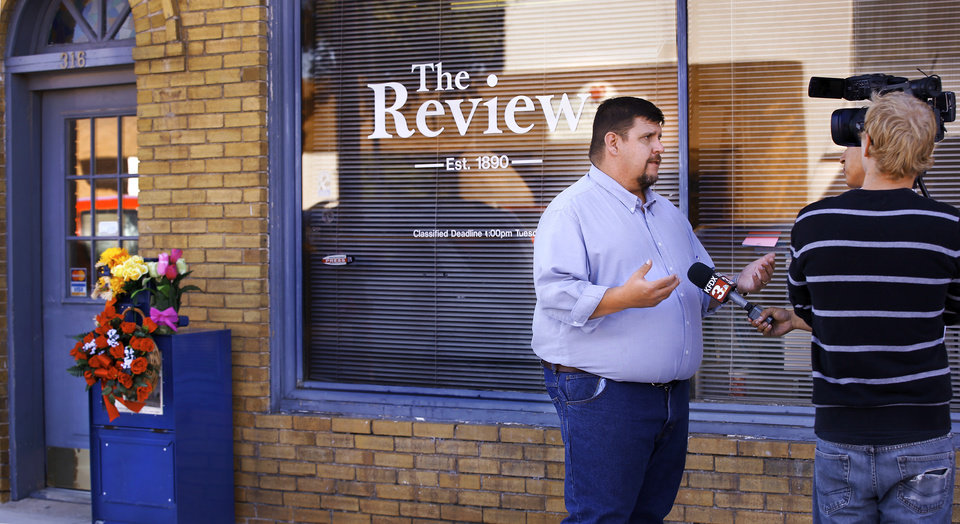 Photo - Todd Brooks is interviewed by a television reporter in front of the offices of  the Marlow Review newspaper on Main Street in downtown Marlow on Tuesday, Oct. 14, 2014. The newspaper was owned by Brooks' boss, John Hruby.   Brooks, a news and sports editor at the newspaper, discussed his reaction to the shocking  discovery of three members of a prominent Duncan family in their home, victims of a triple homicide in an upscale neighborhood on the north side of town Monday morning,  Oct. 13, 2014.  John and Tinker Hruby and their daughter, Katherine,  17, were found dead by the family's housekeeper. Townspeople and customers brought flowers to the paper's office Tuesday, leaving memorial wreaths and plants on a newspaper stand in front of the building.   Photo by Jim Beckel, The Oklahoman