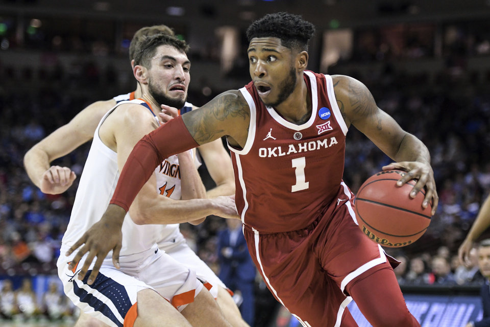 Photo - Oklahoma guard Rashard Odomes (1) drives past Virginia guard Ty Jerome (11) during the first half of a second-round game in the NCAA men's college basketball tournament Sunday, March 24, 2019, in Columbia, S.C. (AP Photo/Sean Rayford)