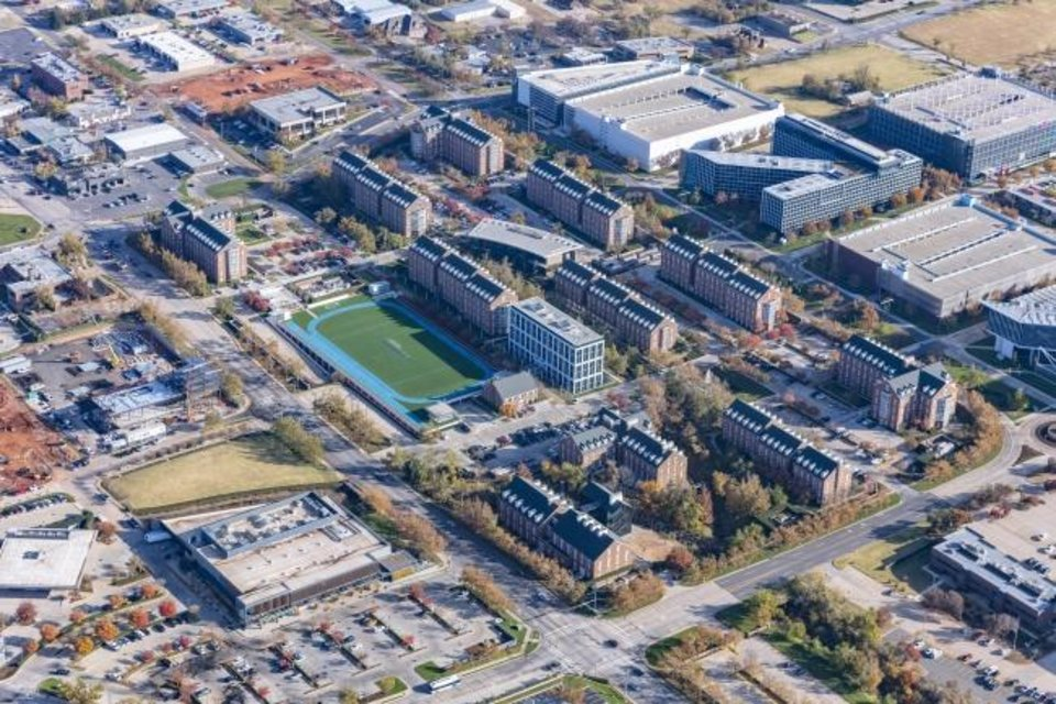 Photo -  The Chesapeake Energy campus represents the vision of the late Aubrey McClendon, who lead the company until 2013. The headquarters consists of Georgian collegiate style buildings (center of photo) and contemporary buildings on the east half of the campus. Commercial development to the south of west of the campus, also originally conceived by McClendon, includes the Whole Foods, lower left, and the Ellison Hotel, being built across from the company's athletic field. [PROVIDED BY CHESAPEAKE ENERGY]