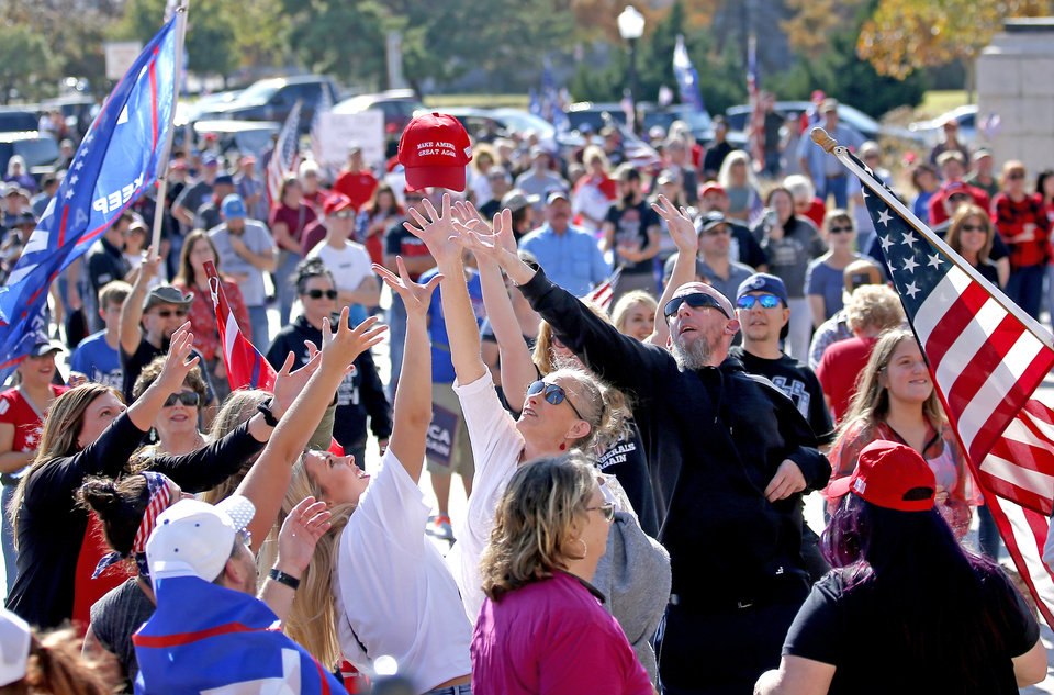 Photo - People try to catch a MAGA hat during a rally for President Trump at the Oklahoma state Capitol in Oklahoma City,  Saturday, Nov. 7, 2020. [Sarah Phipps/The Oklahoman]