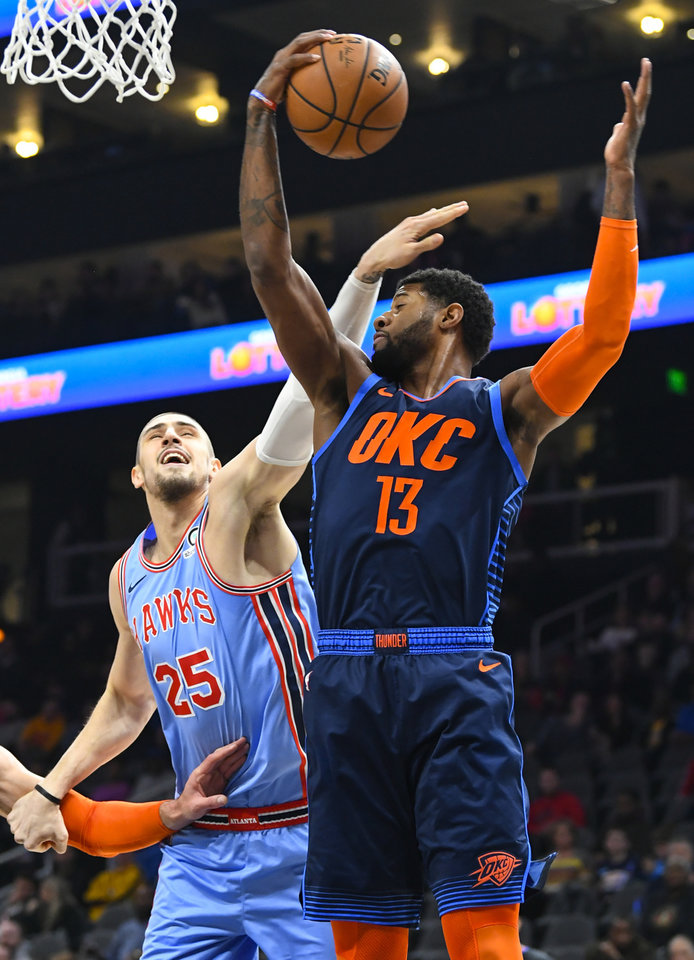 Photo - Oklahoma City Thunder forward Paul George (13) grabs a rebound against Atlanta Hawks center Alex Len (25) during the second half of an NBA basketball game, Tuesday, Jan. 15, 2019 in Atlanta. The Hawks won 142-126. (AP Photo/John Amis)