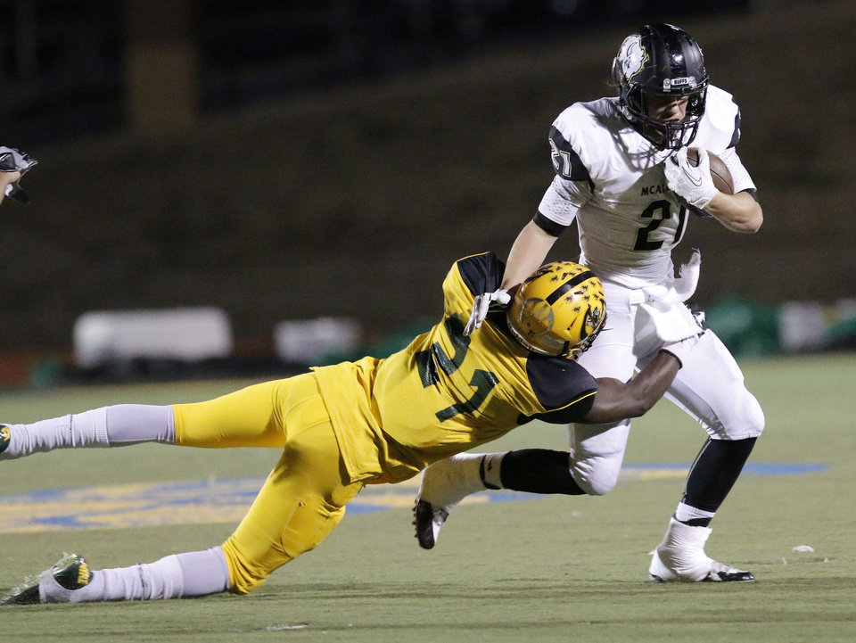 Photo - Mac #21 Davontre Young tackles MHS #21 Rhyln Stephens during the high school football playoff between McAlester and Lawton MacArthur at Choctaw stadium, November 28, 2014. Photo by Doug Hoke, The Oklahoman