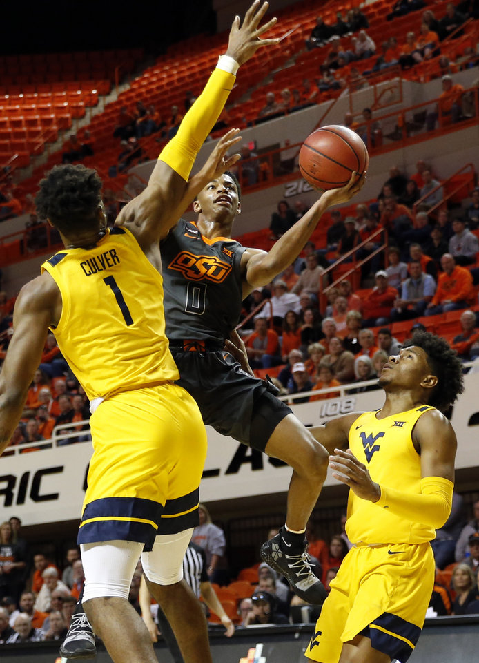 Photo - Oklahoma State's Avery Anderson III (0) tries to score between West Virginia's Derek Culver (1) and Miles McBride (4) in the second half during a men's college basketball game between the Oklahoma State Cowboys and West Virginia Mountaineers at Gallagher-Iba Arena in Stillwater, Okla., Monday, Jan. 6, 2020. West Virginia won 55-41. [Nate Billings/The Oklahoman]