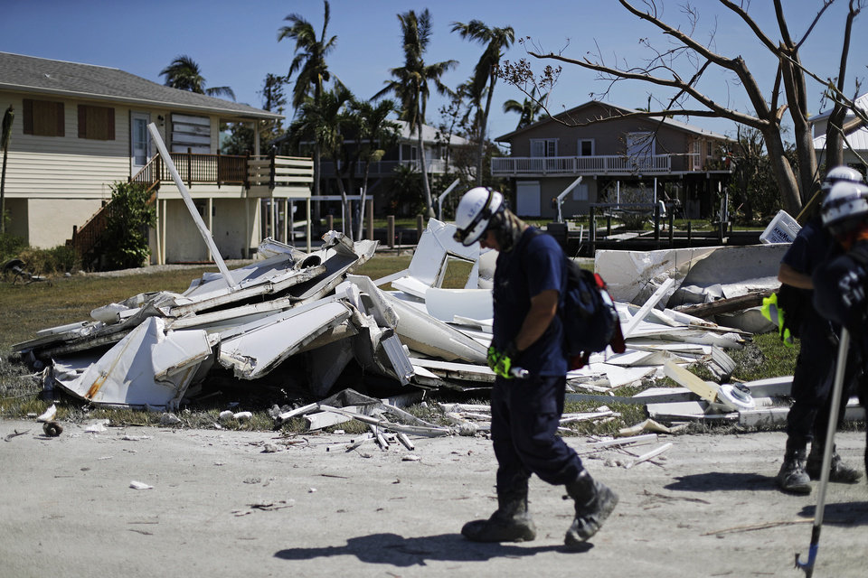 Photo - A member of the Arizona Task Force 1 search and rescue team walks by debris from a home as they knock on doors while checking on homes and their owners after Hurricane Irma in Goodland, Fla., Tuesday, Sept. 12, 2017. (AP Photo/David Goldman)