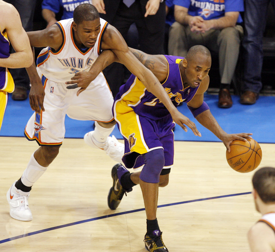 Photo - L.A.'s Kobe Bryant (24) drives the ball away from Oklahoma City's Kevin Durant (35) during the NBA basketball game between the Los Angeles Lakers and the Oklahoma City Thunder in game six of the first round series at the Ford Center in Oklahoma City, Friday, April 30, 2010. L.A. beat Oklahoam City 95-94, winning the series 4-2. [Nate Billings/The Oklahoman]