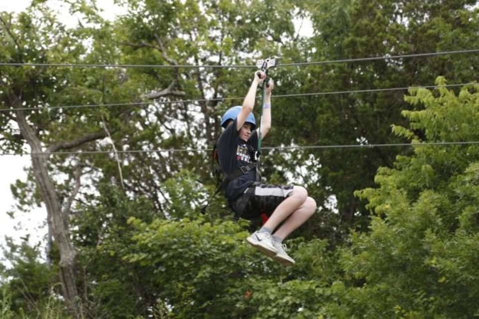 Photo -  A camper ziplines over a lake at Falls Creek.