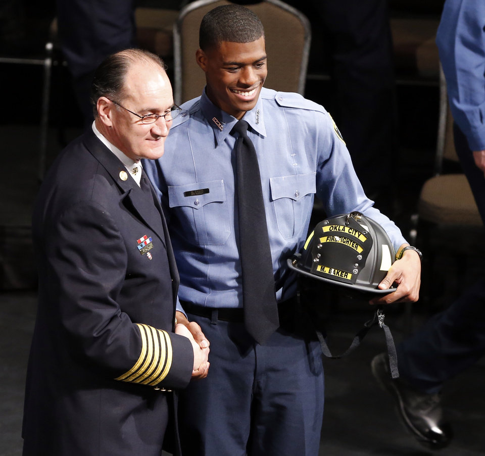Photo -  Malcolm Baker receives his helmet during the Oklahoma City Fire Department Recruit Graduation ceremony at Oklahoma City Community College on Friday. [Photo by Steve Sisney, The Oklahoman]