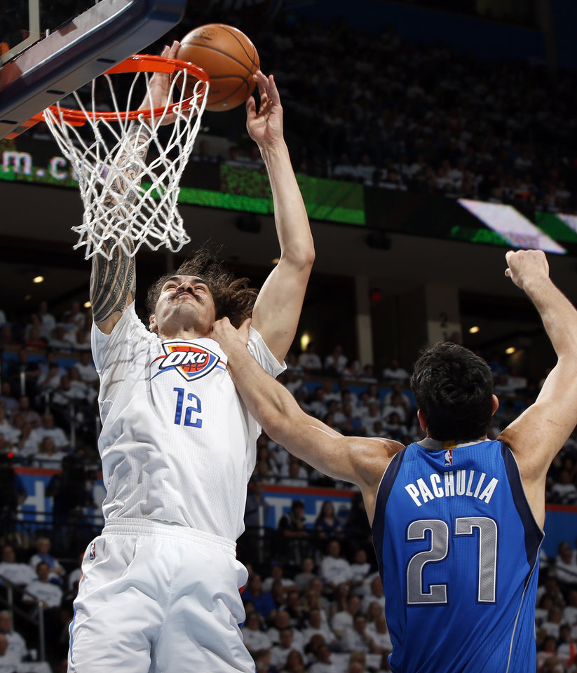 Photo - Oklahoma City's Steven Adams (12) tries to score against Dallas' Zaza Pachulia (27) during Game 2 of the first round series between the Oklahoma City Thunder and the Dallas Mavericks in the NBA playoffs at Chesapeake Energy Arena in Oklahoma City, Monday, April 18, 2016. Photo by Nate Billings, The Oklahoman