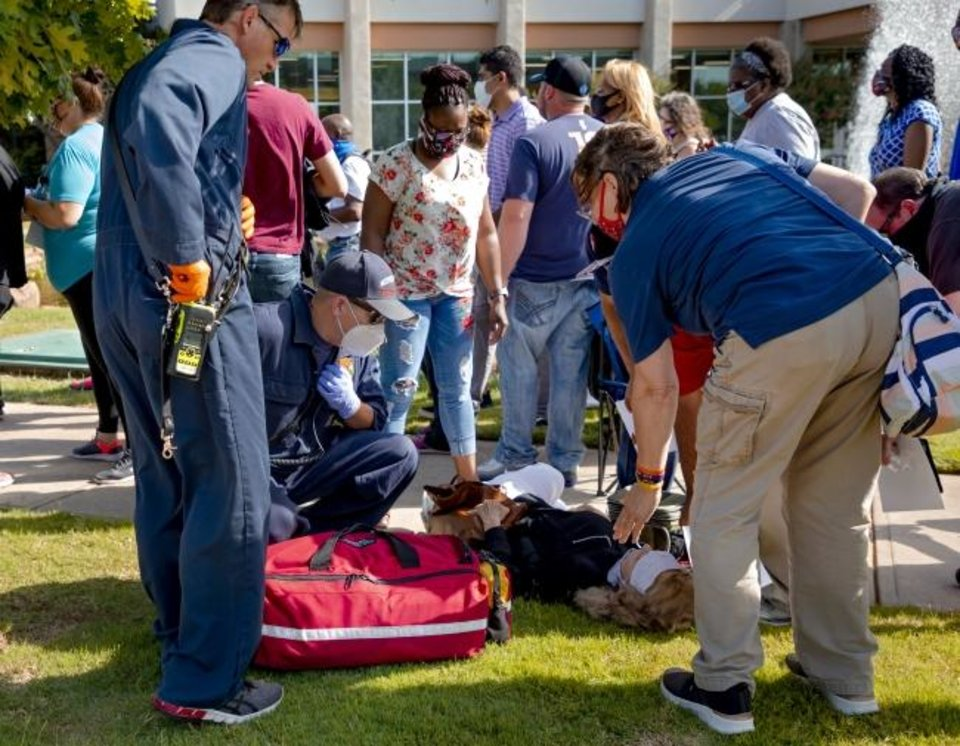 Photo -  Medical personnel help a person struggling with Wednesday's heat as hundreds of people wait in line during the first day of the Oklahoma Employment Security Commission unemployment filing event at the Reed Center in Midwest City. [Chris Landsberger/The Oklahoman]