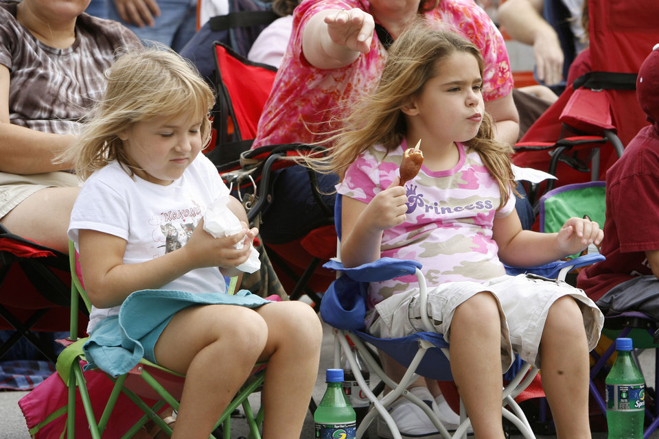Photo - Five year old Kennedy Poe and six year old Hayden Mennella enjoy corn dogs during the Oklahoma Centennial Parade in downtown Oklahoma City, Okla., Sunday, October 14, 2007. Photo by Paul Hellstern / The Oklahoman.