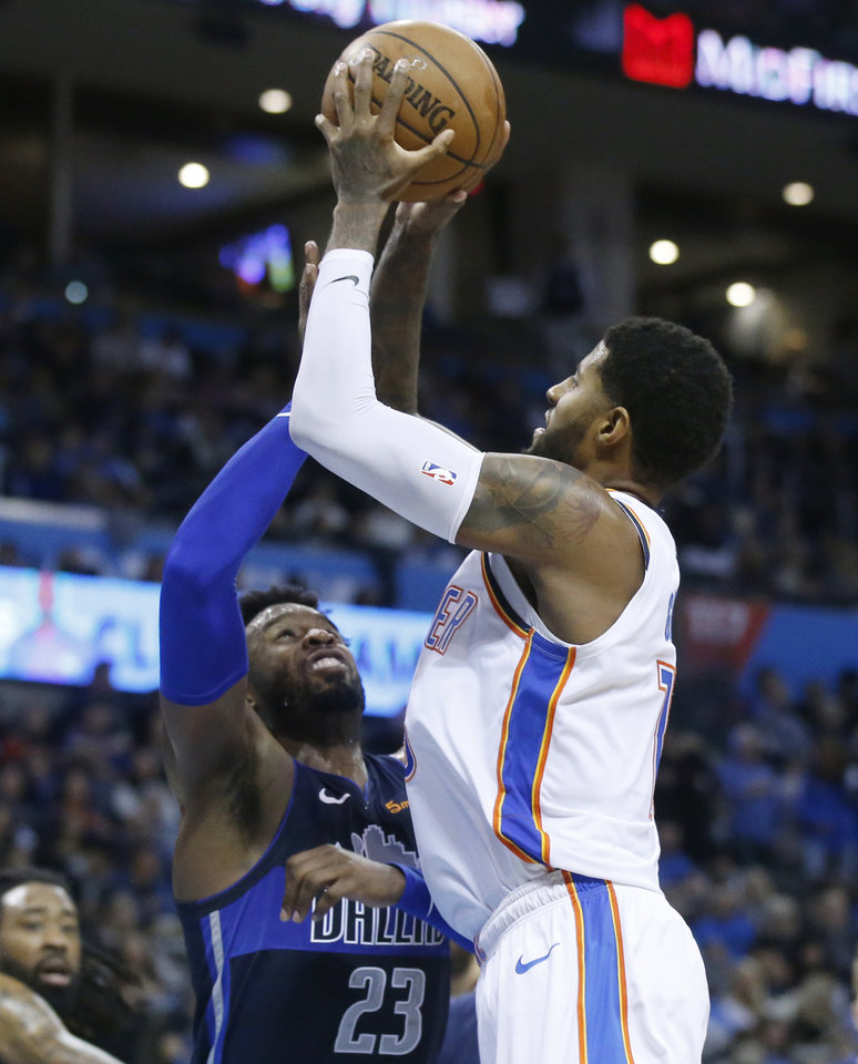Photo - Oklahoma City Thunder forward Paul George, right, shoots as Dallas Mavericks guard Wesley Matthews (23) defends in the second half of an NBA basketball game in Oklahoma City, Monday, Dec. 31, 2018. (AP Photo/Sue Ogrocki)