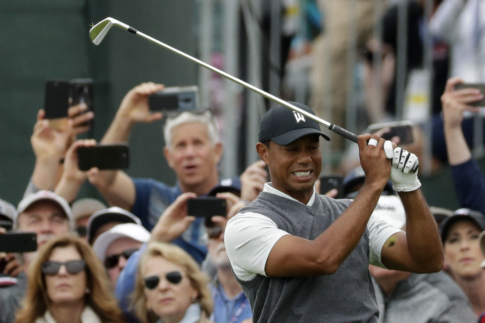 Photo -  Tiger Woods reacts after his tee shot on the fifth hole during the first round of the U.S. Open Championship in Pebble Beach, Calif. [AP Photo/Matt York]