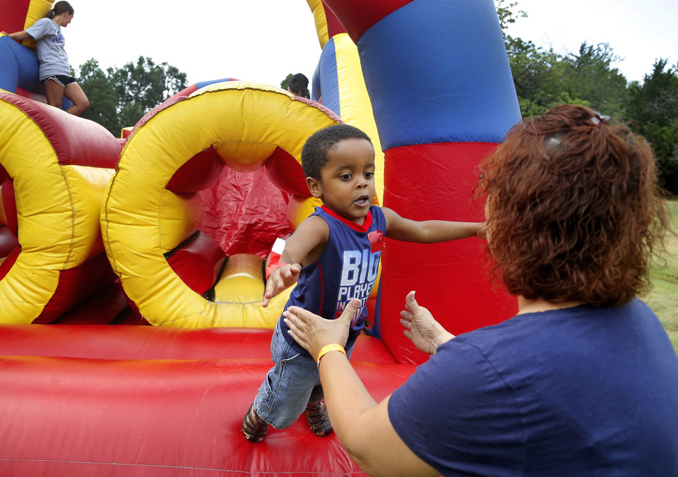 Photo - A small boy jumps into the arms of a volunteer after making it through the inflatable obstacle course. Redeeming the Family, a nonprofit organization, hosted an Outdoor Adventure Day event for children who have a parent currently serving a prison term. The event was July 19 at John Nichols Scout Ranch in Mustang. The children rotated through a variety of activities and were treated to lunch at the camp.  Photo by Jim Beckel, The Oklahoman  Jim Beckel -  THE OKLAHOMAN