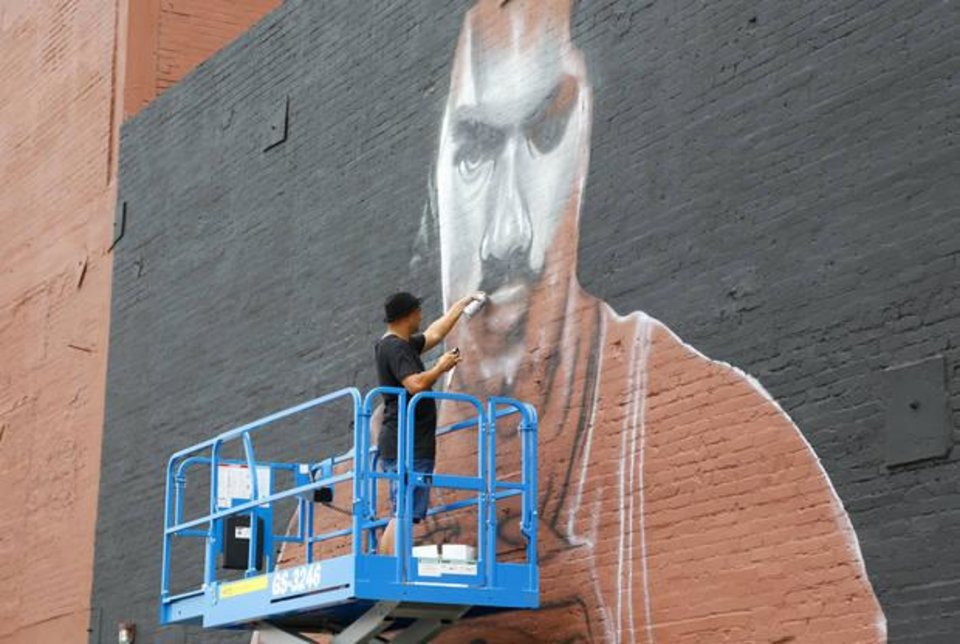 Photo - Graham Hoete, a New Zealander artist living in Australia who is visiting the United States, spray paints a mural of Thunder center Steven Adams on a wall of The Paramount in Oklahoma City, Monday, June 13, 2016. Photo by Kurt Steiss, The Oklahoman