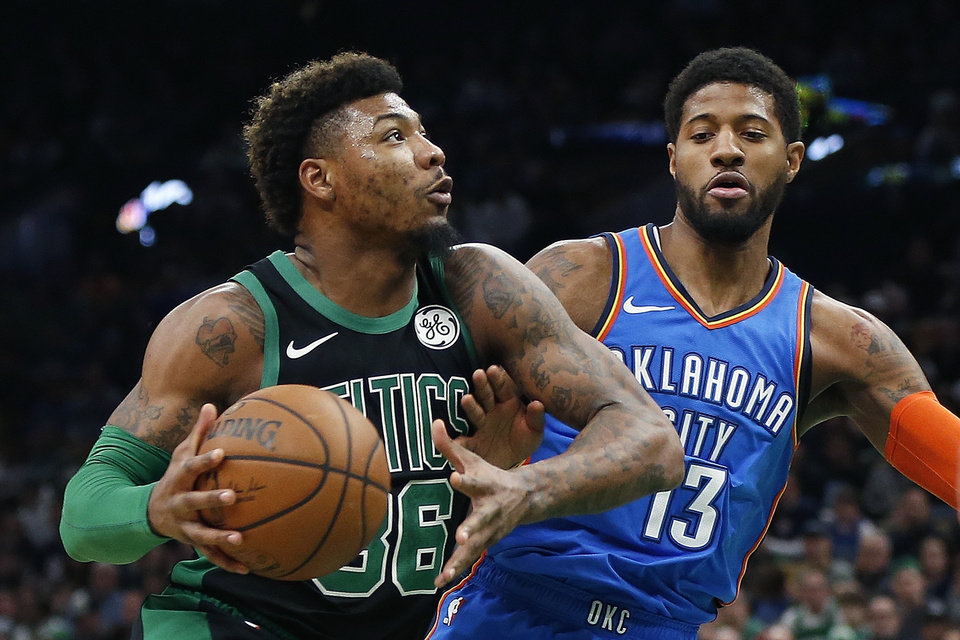 Photo - Boston Celtics' Marcus Smart (36) drives for the basket against Oklahoma City Thunder's Paul George (13) during the first half of an NBA basketball game in Boston, Sunday, Feb. 3, 2019. (AP Photo/Michael Dwyer)