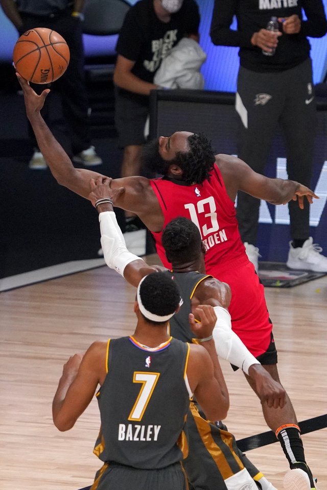 Photo - Oklahoma City Thunder's Darius Bazley (7) watches as Nerlens Noel attempts to stop Houston Rockets' James Harden (13) on a shot attempt during the second half of an NBA first-round playoff basketball game, Monday, Aug. 31, 2020, in Lake Buena Vista, Fla. (AP Photo/Mark J. Terrill)