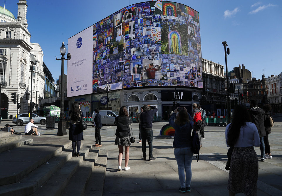 Photo -  People watch as pictures appear on a screen during a 10 minute domination on The Piccadilly Lights, Piccadilly Circus, to mark the launch of The People's Picture interactive mosaic art project Rainbows for the NHS in London, Monday, June 22, 2020. The art installation which features thousands of photos and messages from key workers, carers, patients, doctors and nurses appears on Piccadilly Lights until June 28.(AP Photo/Frank Augstein)