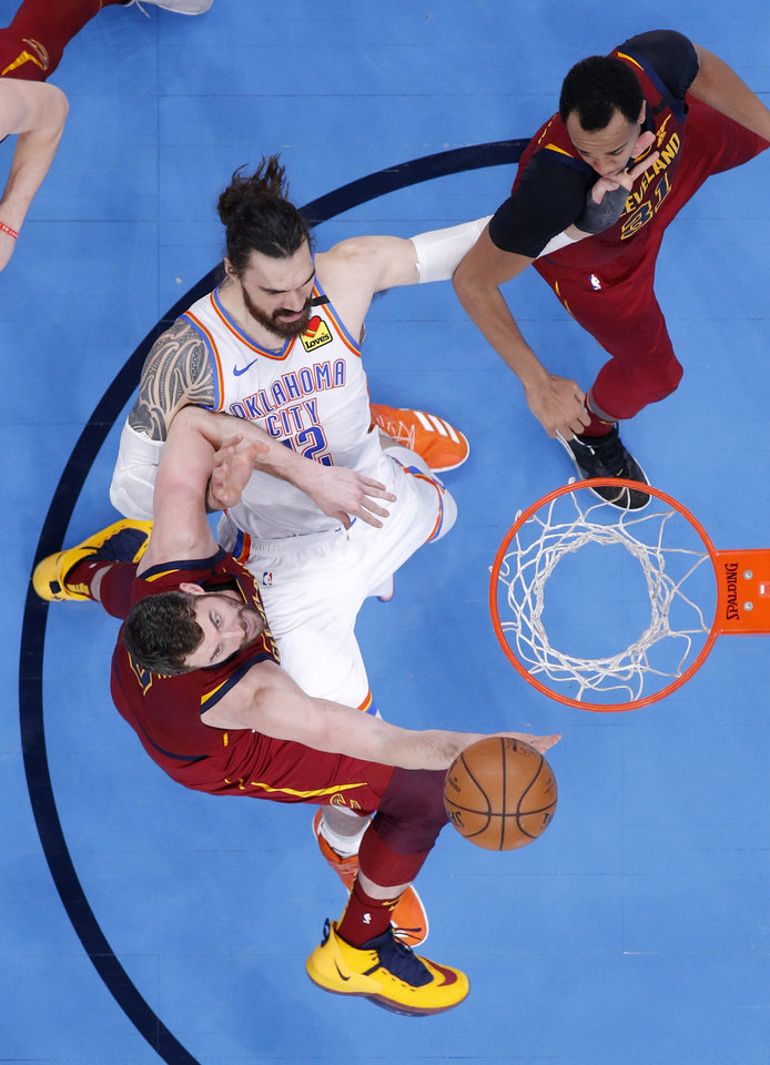 Photo - Oklahoma City's Steven Adams (12) fights for a rebound between Cleveland's Kevin Love (0) and John Henson (31) during an NBA basketball game between the Oklahoma City Thunder and the Cleveland Cavaliers at Chesapeake Energy Arena in Oklahoma City, Wednesday, Feb. 5, 2020. Oklahoma City won 109-103. [Bryan Terry/The Oklahoman]