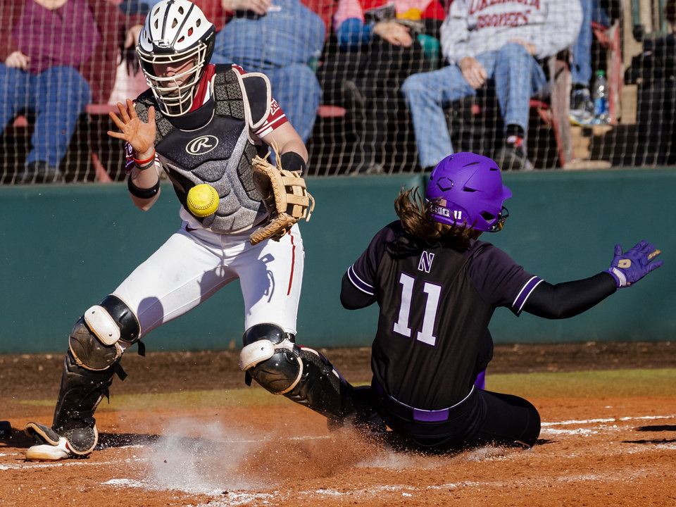 Photo - Northwestern's Rachel Lewis (11) scores a run past Oklahoma's Lynnsie Elam (22) during the college softball game between the University of Oklahoma Sooners (OU) and Northwester University Wildcats (NU) at Marita Hynes Field in Norman, Okla. on Friday, Feb. 28, 2020.    [Chris Landsberger/The Oklahoman]