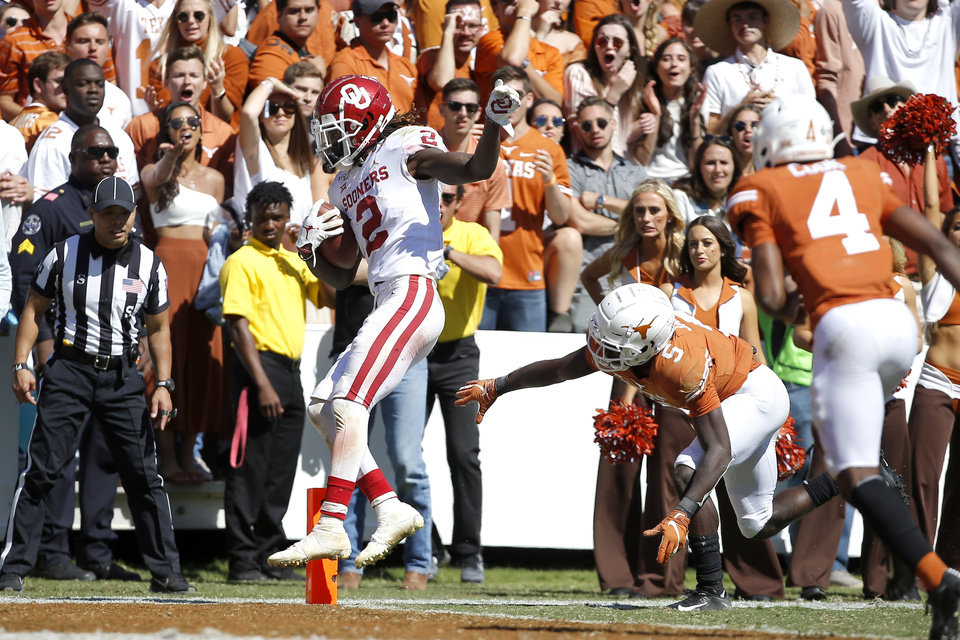 Photo - Oklahoma's CeeDee Lamb (2) scores a touhcdown in front of Texas defensive back D'Shawn Jamison (5) during the Red River Showdown college football game between the University of Oklahoma Sooners (OU) and the Texas Longhorns (UT) at Cotton Bowl Stadium in Dallas, Saturday, Oct. 12, 2019. Oklahoma won 34-27. [Bryan Terry/The Oklahoman]