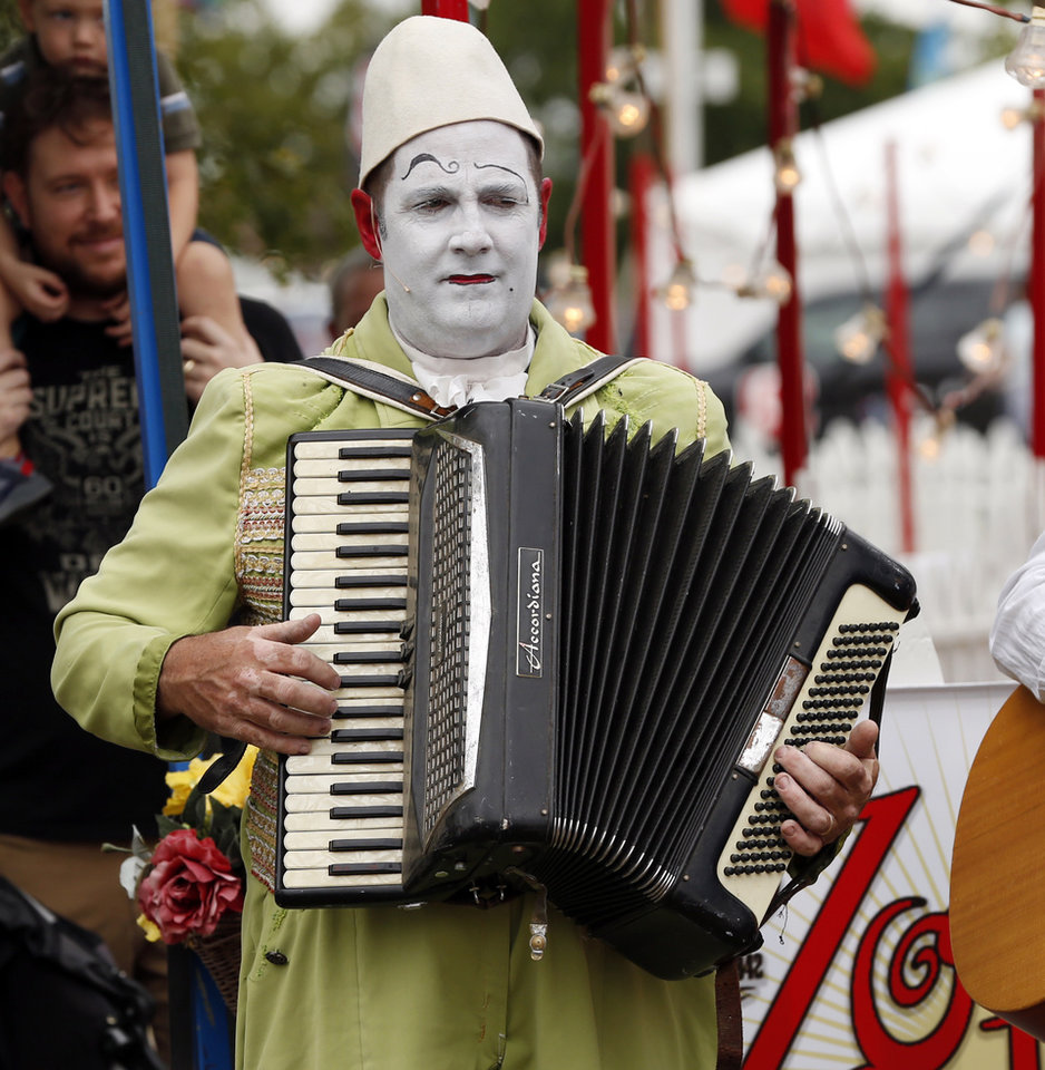 Photo -  A musician plays for the crowd waiting to see Zoppe Circus at the Oklahoma State Fair on Thursday. [Photos by Steve Sisney, The Oklahoman]