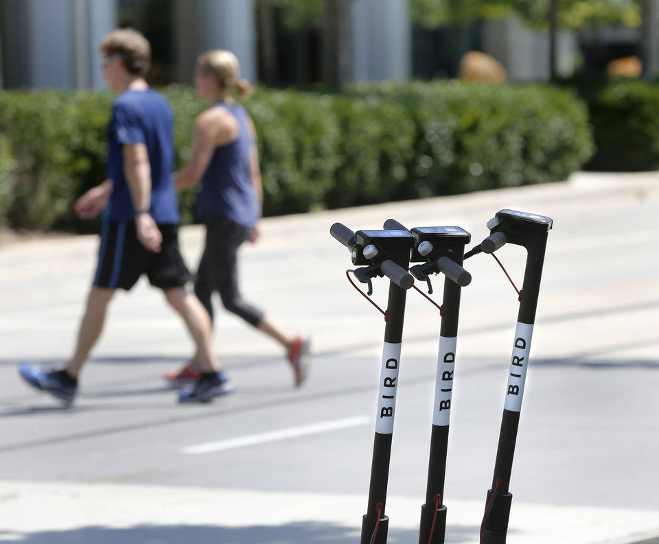 Photo - Bird motorized scooters parked on W. Sheridan, in front of the Devon Tower and Myriad Gardens on Thursday. [Photo by Jim Beckel, The Oklahoman]