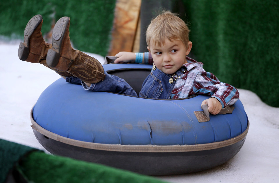 Photo -  Lane Hern, then 5, rides down a snow slide during the 2015 Snow Tubing Winter Festival at Chickasaw Bricktown Ballpark in Oklahoma City. [Photo by Bryan Terry, The Oklahoman Archives]